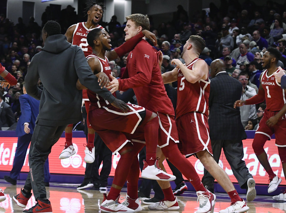 Photo - Oklahoma players celebrate after defeating Northwestern 76-69 in overtime in an NCAA college basketball game Friday, Dec. 21, 2018, in Evanston, Ill. (AP Photo/Matt Marton)