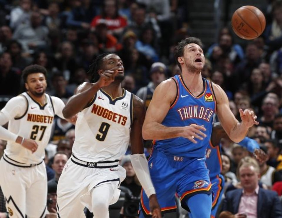 Photo -  Nuggets forward Jerami Grant, left, and Thunder forward Danilo Gallinari chase a loose ball in the first half of Denver's 110-102 win Saturday. [AP Photo/David Zalubowski]