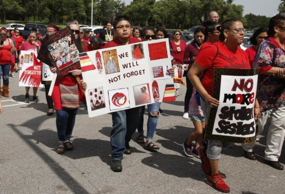 Photo -  Jonathan Sam of Stillwater, a native Navajo and Zuni, joins a march to call for justice for missing and murdered indigenous women in June 14 at the Cheyenne and Arapaho Tribes of Oklahoma in Concho. [Sue Ogrocki/The Associated Press]