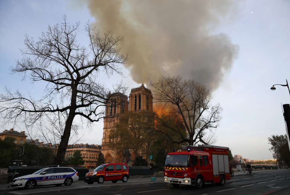 Photo - A polcie car and fire brigade vehicles park while Notre Dame cathedral is burning in Paris, Monday, April 15, 2019. Massive plumes of yellow brown smoke is filling the air above Notre Dame Cathedral and ash is falling on tourists and others around the island that marks the center of Paris. (AP Photo/Francois Mori)