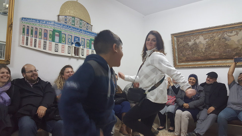 Photo - A young Palestinian boy dances with Kathy Dodd of Tulsa after a meal of Maklouba during the Oklahoma Religions United group's trip to Israel and the Palestinian Territories. [Photo by Carla Hinton, The Oklahoman]