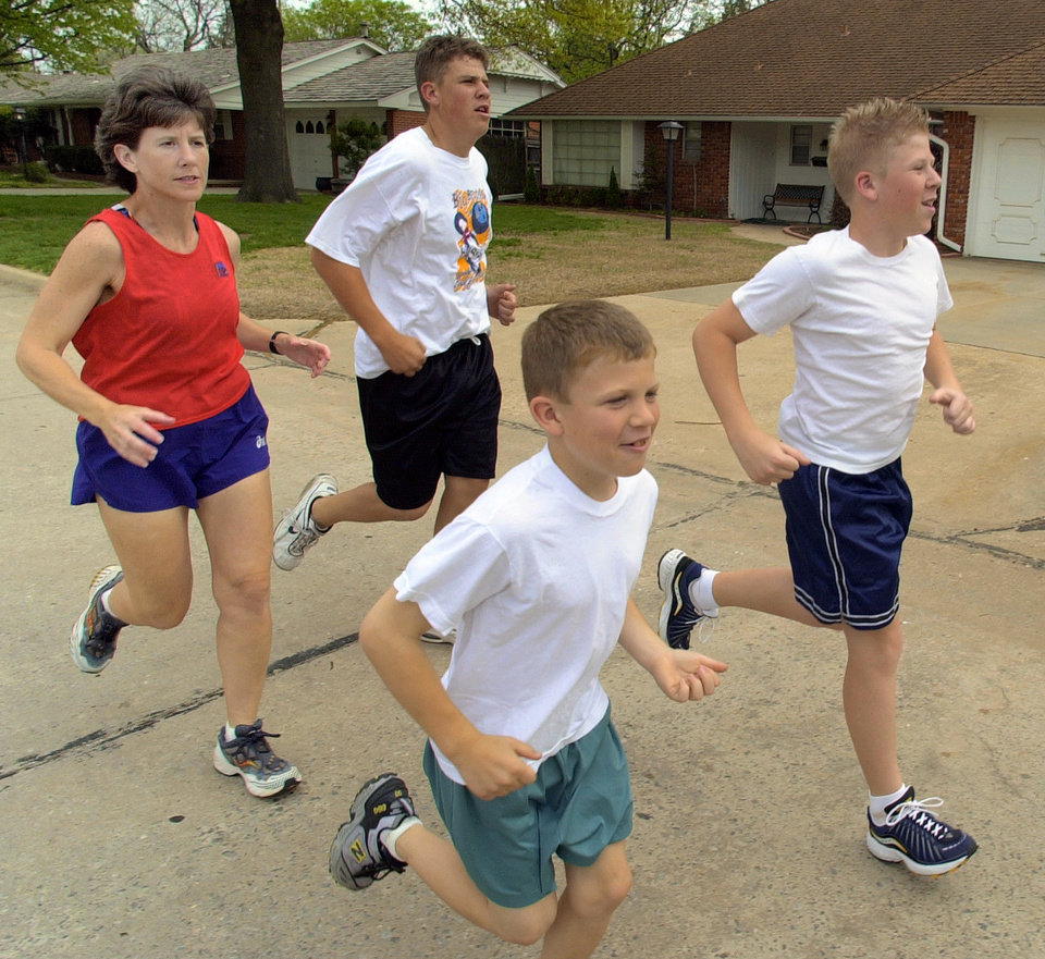 Photo - (l to r) Mariana Birchell runs with her sons Brian, 18, Jeffrey, 10, Mark, 14, near her home in NW Oklahoma City. The family has entered the Oklahoma City Memorial Marathon. For Klinka story. Staff photo by Nate Billings.