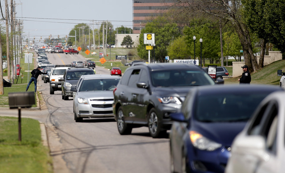 Photo - Traffic is lined up on Britton Road near  People's Church, 800 E. Britton Rd., in Oklahoma City, Thursday, April 9, 2020. Cars lined up for miles and hours as the church members gave away 6,000 pounds of free groceries and supplies. [Sarah Phipps/The Oklahoman]