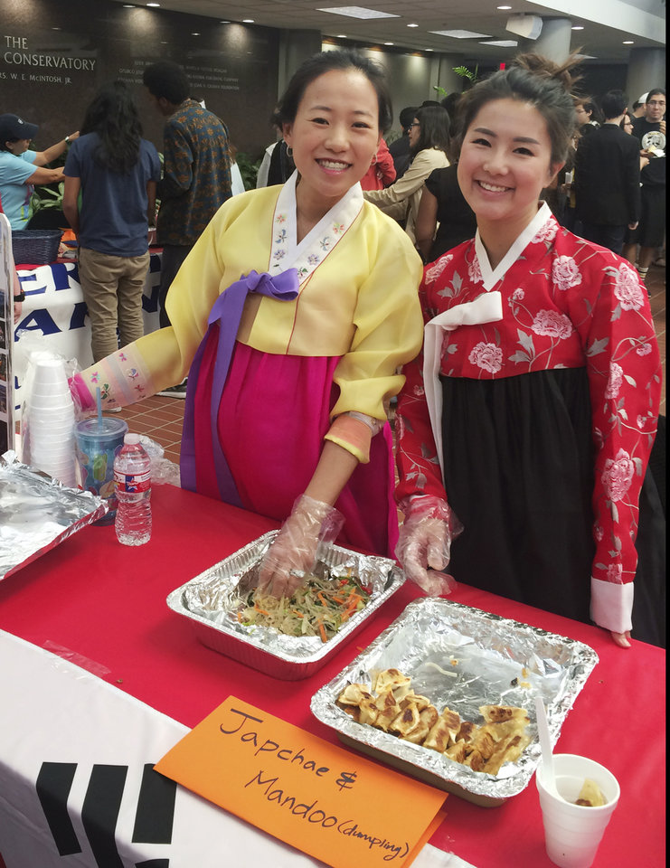 Photo -  From left, Sophia Lee and Lucy Kang take a break from serving traditional South Korean dishes such as Japchae and Mandoo to show off their hanboks. Lee wore her colorful dress to her wedding and explained that hanboks are worn on special occasions, such as weddings and funerals.