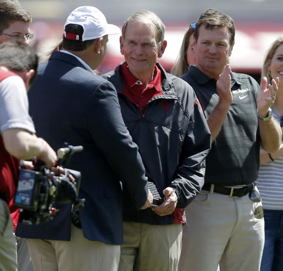 Photo -  Merv Johnson is recognized by athletic director Joe Castiglione, left, and coach Bob Stoops during OU's 2017 spring game. Johnson, a former Oklahoma football coach and current radio broadcast analyst for Sooner games, was seriously injured in a car accident on Sunday. [Photo by Bryan Terry/The Oklahoman]