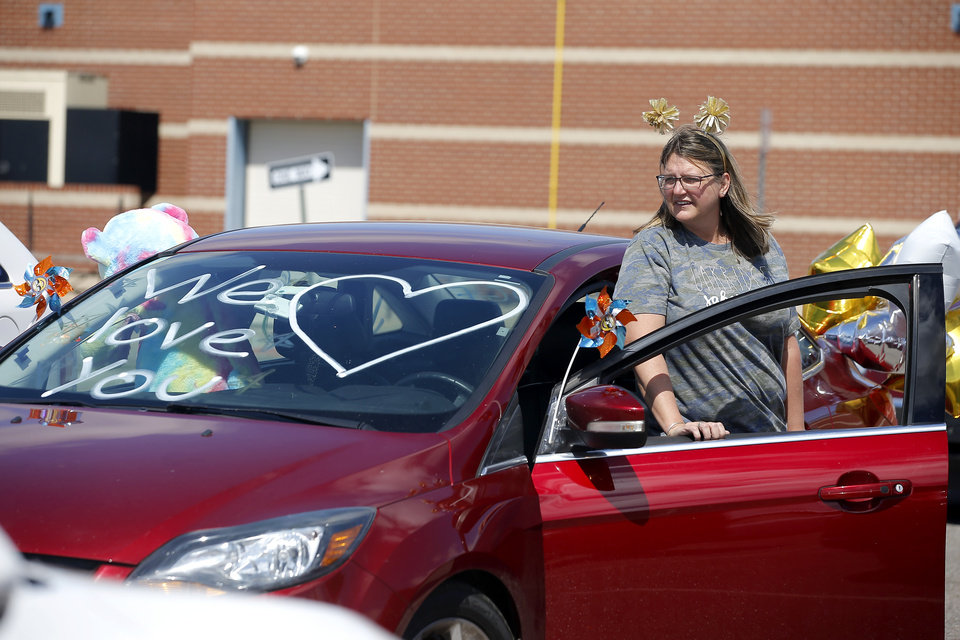 Photo - Michelle Flipski, a kindergarten teacher assistant, gets in her car before starting an  Oakridge Elementary faculty caravan through neighborhoods around the Moore school, Tuesday, March 24, 2020. [Bryan Terry/The Oklahoman]