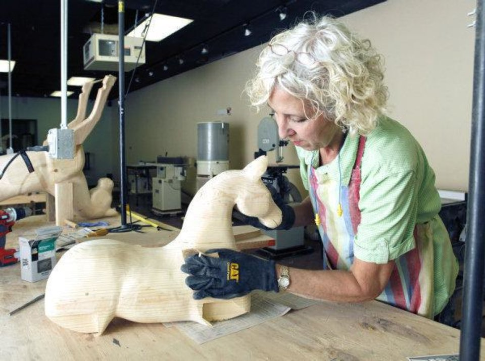 Photo - Jackie Wilson sands one of her rocking horses at her shop on Broadway in downtown Edmond. PHOTO BY PAUL HELLSTERN, THE OKLAHOMAN  PAUL HELLSTERN