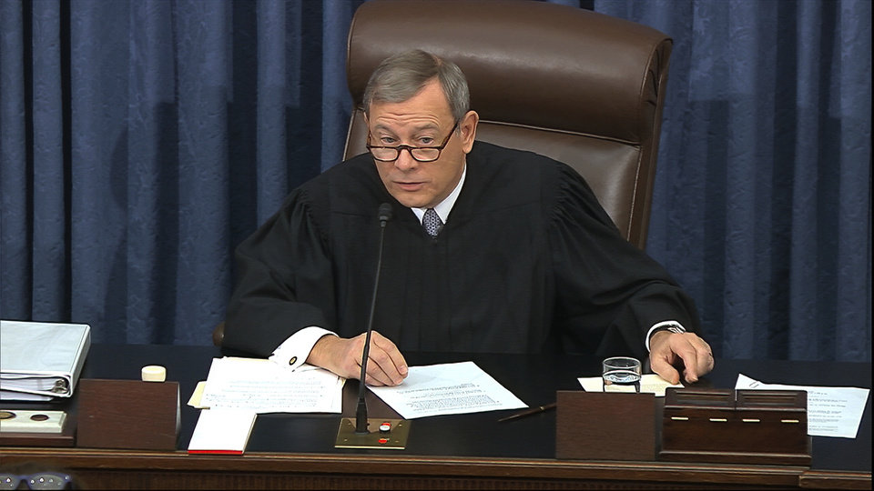 Photo -  In this image from video, presiding officer Chief Justice of the United States John Roberts gets a card with the question submitted by Sen. Rand Paul, R-Ky., aside as declines to read the question as written during the impeachment trial against President Donald Trump in the Senate at the U.S. Capitol in Washington, Thursday, Jan. 30 2020. (Senate Television via AP)