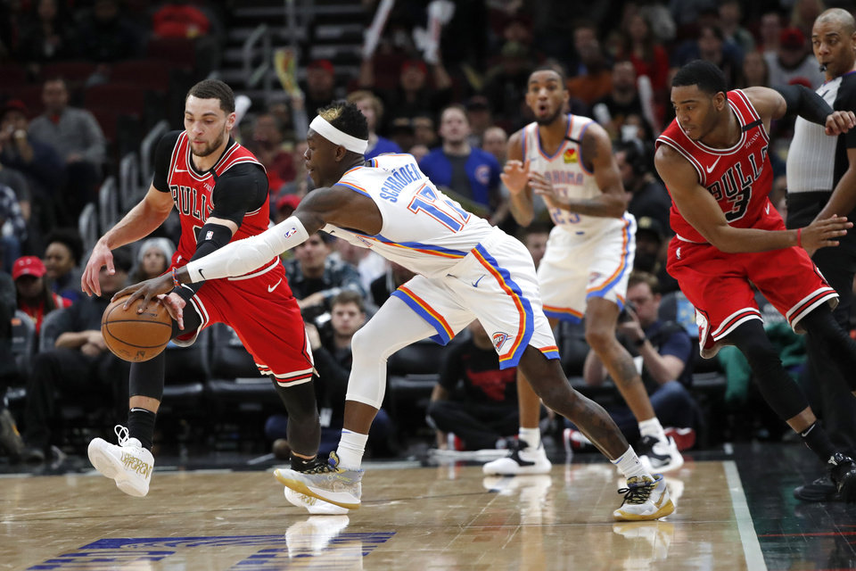 Photo - Chicago Bulls' Zach LaVine, left, steals the ball from Oklahoma City Thunder's Dennis Schroder, as Shaquille Harrison (3) watches, during the second half of an NBA basketball game Tuesday, Feb. 25, 2020, in Chicago. The Thunder won 124-122. (AP Photo/Charles Rex Arbogast)
