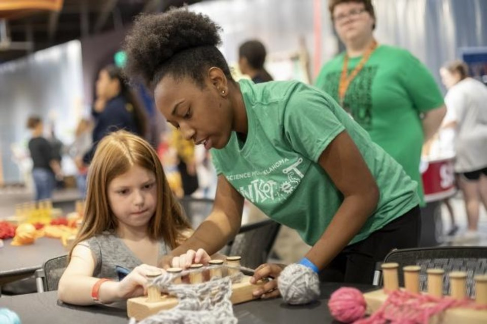 Photo -  A volunteer helps a child with loom knitting during the 2018 Tinkerfest. [PHOTO PROVIDED]
