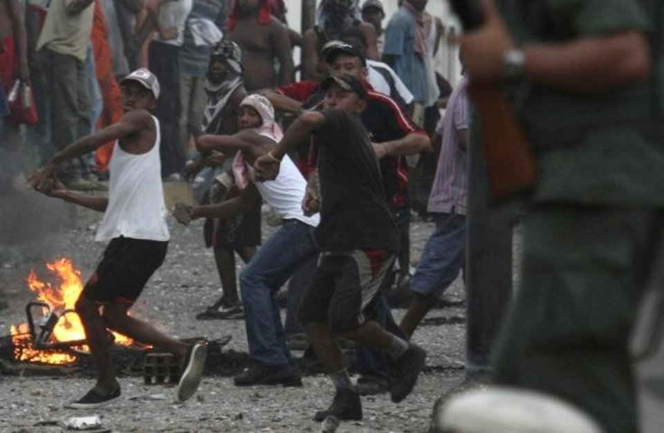Photo -  Protesters throw stones during clashes with National Guard soldiers in Curiepe, Venezuela. Clashes between troops and protesters there have brought about international sanctions against the country, making it hard for U.S. business to operate there. [AP PHOTO]
