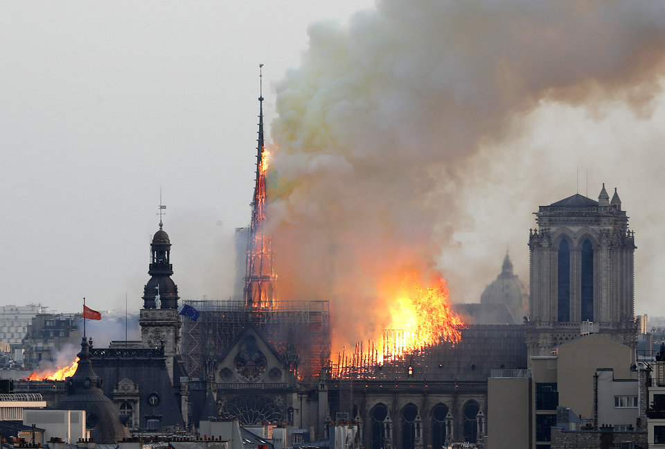 Photo - Flames rise from Notre Dame cathedral as it burns in Paris, Monday, April 15, 2019. Massive plumes of yellow brown smoke is filling the air above Notre Dame Cathedral and ash is falling on tourists and others around the island that marks the center of Paris. (AP Photo/Thibault Camus)