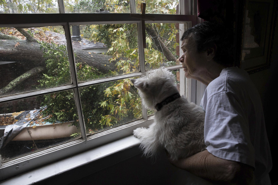 Photo - Eighty eight-year-old Martha Jane Jones, holding her dog, Molly, poses for a photo while looking out at a tree that fell on her neighbors home, Wednesday, Nov. 30, 2016, in Atlanta. The National Weather Service says a tornado has touched down near Atlanta as heavy storms continue to sweep through parts of the southern region. (Branden Camp/Atlanta Journal-Constitution via AP) (Branden Camp/Atlanta Journal-Constitution via AP)