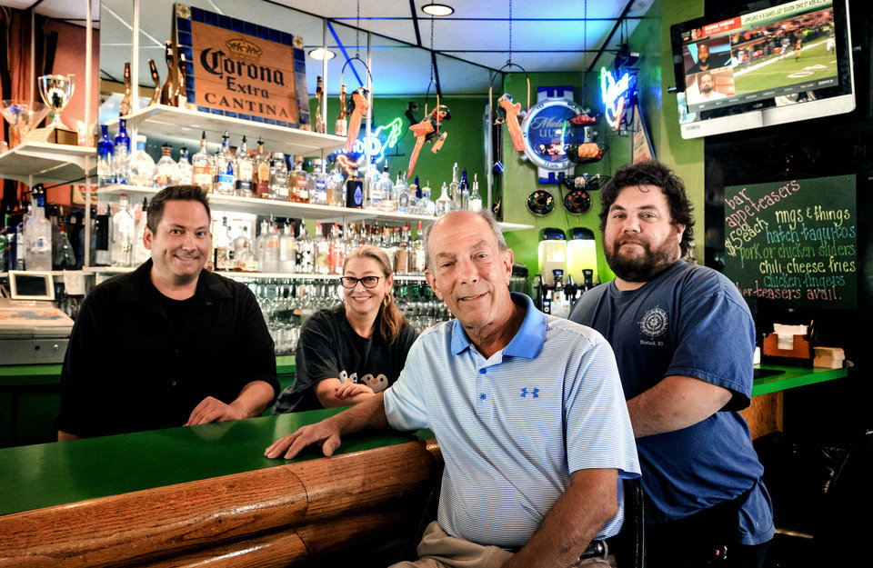 Photo -  Howie Shiff, center, owner of Mamasita's stands at the bar with Doug Barton, left, Jennifer Johnston and Aaron Shiff at the restaurant, which is scheduled to close after 32 years. [Photo by Chris Landsberger, The Oklahoman]