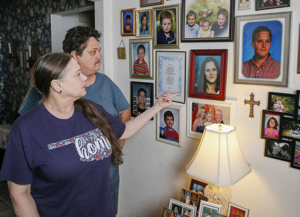 Photo - Mary Perryman and her husband, Woody Perryman, look at family photos at their home in Oklahoma City, Wednesday, March 4, 2020. Mary and Woody Perryman met at a support group for relatives of homicide victims. Mary's murdered sister, Jennifer Sipes, is shown in the large photo in the center. Woody's murdered son, Brandon Perryman, is shown in the large photo at right. [Nate Billings/The Oklahoman]