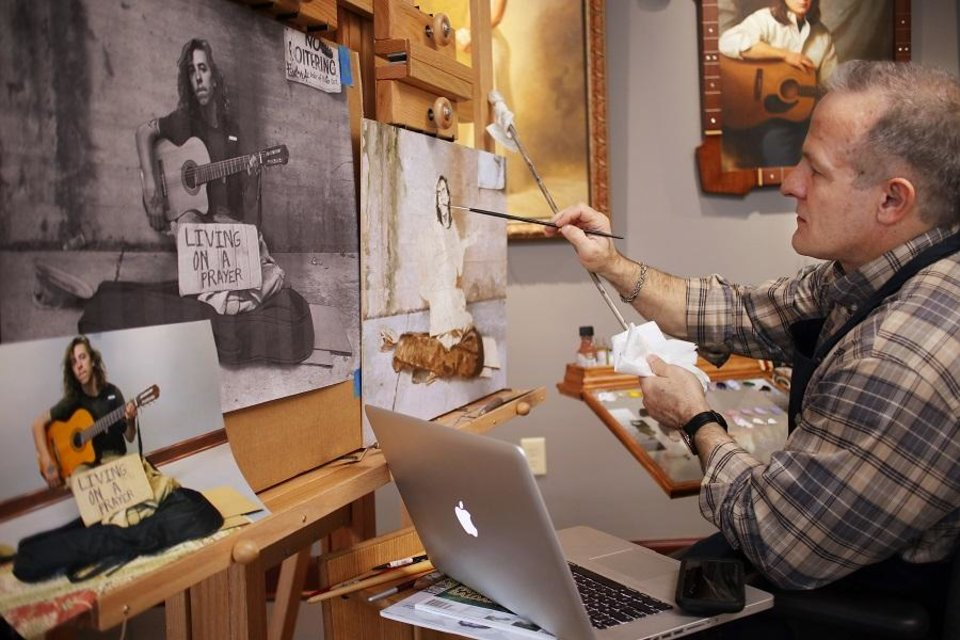 Photo - Mike Wimmer works on a painting in his