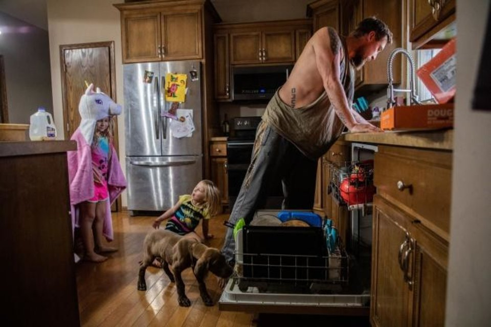 Photo -  Adam Seidler makes breakfast for daughters Paisley, 4, and Addy, 8, left, with their dog, Mac, at home in Diamond, Illinois. [CHICAGO TRIBUNE/TNS]