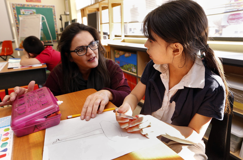 Photo -  Ayline Saenz-Gomez, first grade, gets help from Linda Lopez on Wednesday at Hawthorne Elementary School in Oklahoma City.