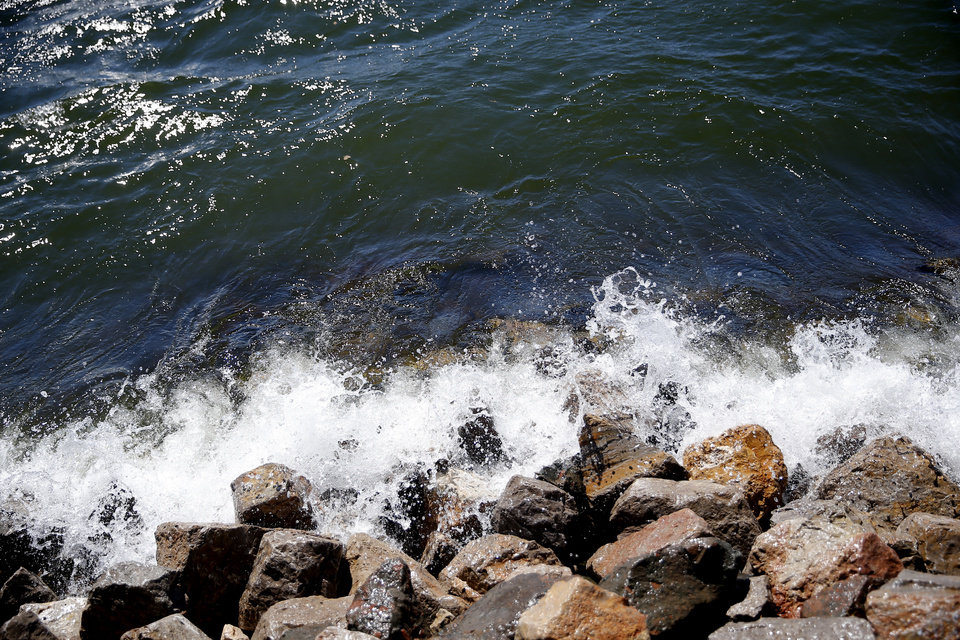 Photo - Waves hit the rocks during high winds at Lake Hefner in Oklahoma City,  Wednesday, March 13, 2019. Photo by Sarah Phipps, The Oklahoman