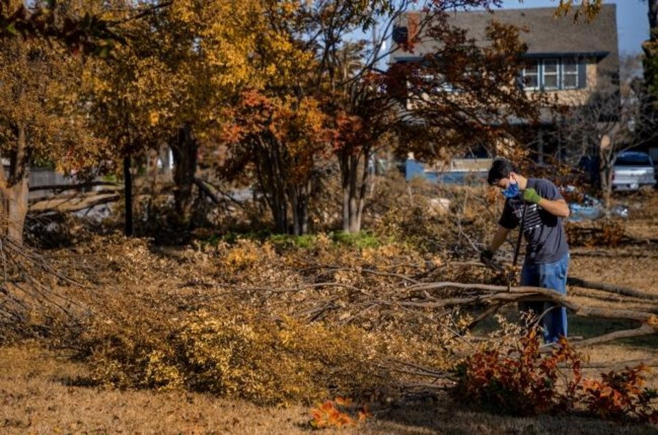 Photo -  Jonathan Beckstrand, a Church of Jesus Christ of Latter-day Saints missionary, joined a group of missionaries working to clean up storm damage at Perle Mesta Park on Friday in Oklahoma City. [Chris Landsberger/The Oklahoman]