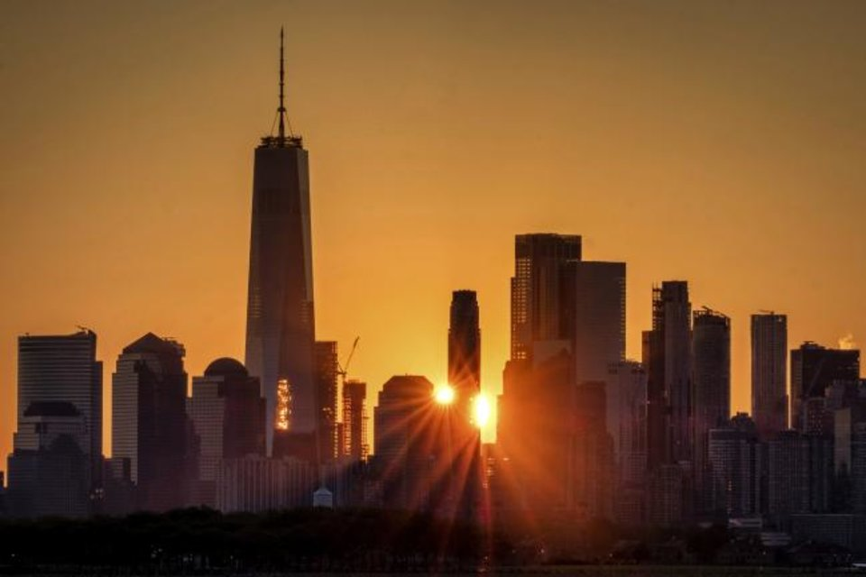 Photo -  The sunlight flares around the buildings in lower Manhattan as the sun rises in New York. [AP PHOTO]