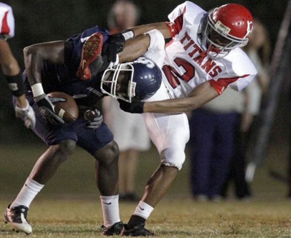 Photo -  Shawnee's Gabrion Frazier (1) and Carl Albert's Dwight Dobbins (2) get tangled up following a play during the high school football game between Shawnee and Carl Albert Friday, 0ct. 2, 2009, at the Jim Thorpe Stadium in Shawnee, Okla. Photo by Sarah Phipps, The Oklahoman