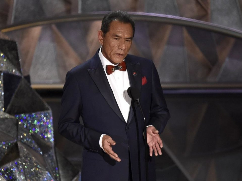 Photo - Wes Studi introduces a tribute to films that honor service in the military at the Oscars on Sunday, March 4, 2018, at the Dolby Theatre in Los Angeles. [Photo by Chris Pizzello/Invision/AP]