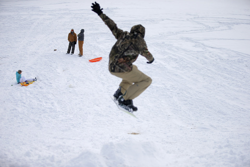 Photo - Sledders watch as a snowboarder flies through the air on a hill along W Hefner Road in Oklahoma City after a winter storm dropped another layer of snow in Oklahoma City, Wednesday, Feb. 17, 2021. [Bryan Terry/The Oklahoman]