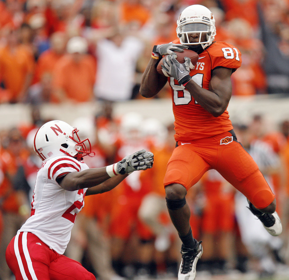 Photo - OSU's Justin Blackmon (81) makes a catch next to Prince Amukamara (21) of Nebraska on the way to an 80-yard touchdown in the second quarter during the college football game between the Oklahoma State Cowboys (OSU) and the Nebraska Huskers (NU) at Boone Pickens Stadium in Stillwater, Okla., Saturday, Oct. 23, 2010. Photo by Nate Billings, The Oklahoman