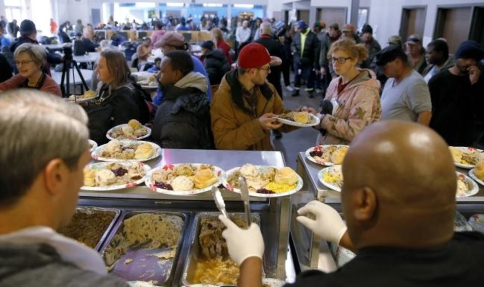 Photo -  Experts say those who help others were most likely to thrive. Volunteers fill plates with food in November during the Homeless Alliance Thanksgiving dinner at the WestTown day shelter in Oklahoma City. [Bryan Terry/The Oklahoman Archive]
