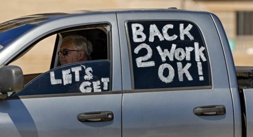 Photo -  A protester drives his car during the Let's Get Oklahoma Open For Business rally at the Oklahoma State Capitol in Oklahoma City, Okla. on Wednesday, April 15, 2020. Participants drove their cars around the Capitol to protest the hardship Oklahoma citizens are being placed in due to businesses being forced to close during the COVID-19 pandemic.  [Chris Landsberger/The Oklahoman]
