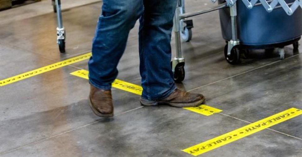 Photo - Yellow tape marks the space of six feet to separate workers as the gather food items to fill food boxes at the Regional Food Bank of Oklahoma in Oklahoma City, Okla. on Friday, March 20, 2020.  [Chris Landsberger/The Oklahoman]