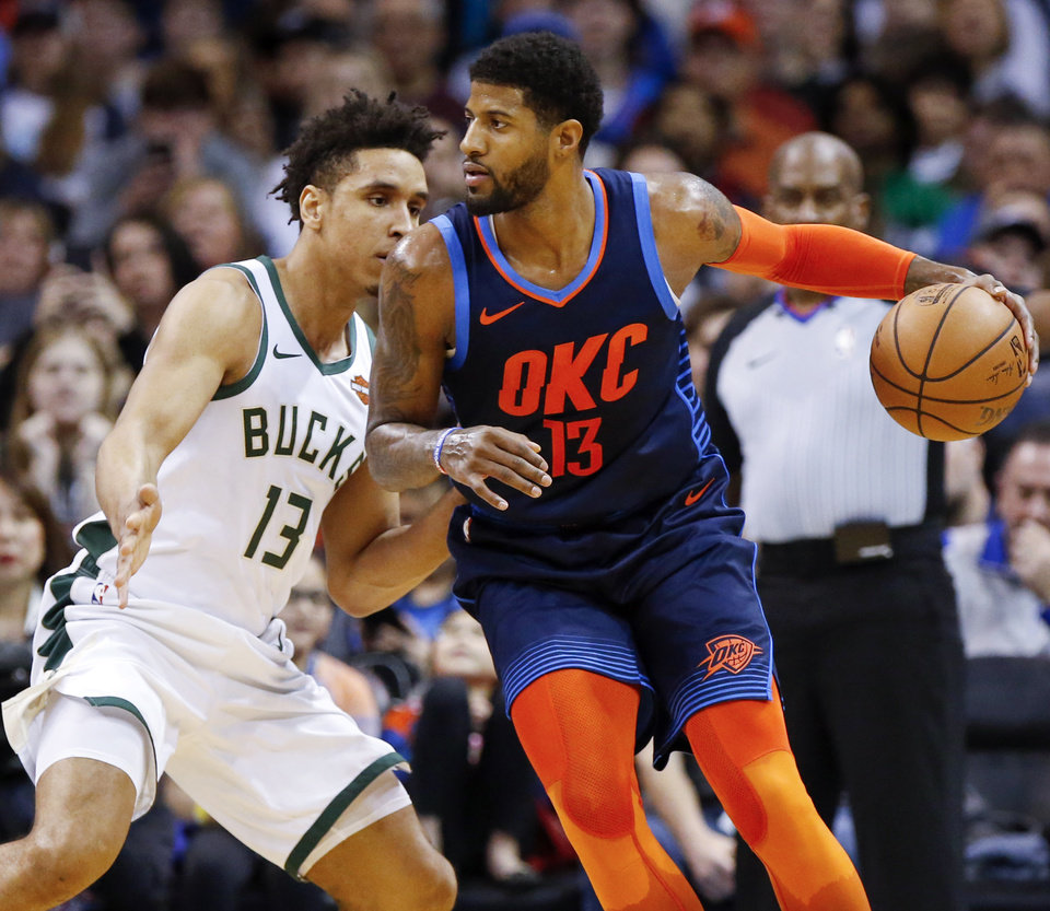 Photo - Oklahoma City's Paul George (13) dribbles as Milwaukee's Malcolm Brogdon (13) defends during an NBA basketball game between the Milwaukee Bucks and the Oklahoma City Thunder at Chesapeake Energy Arena in Oklahoma City, Sunday, Jan. 27, 2019. Photo by Nate Billings, The Oklahoman