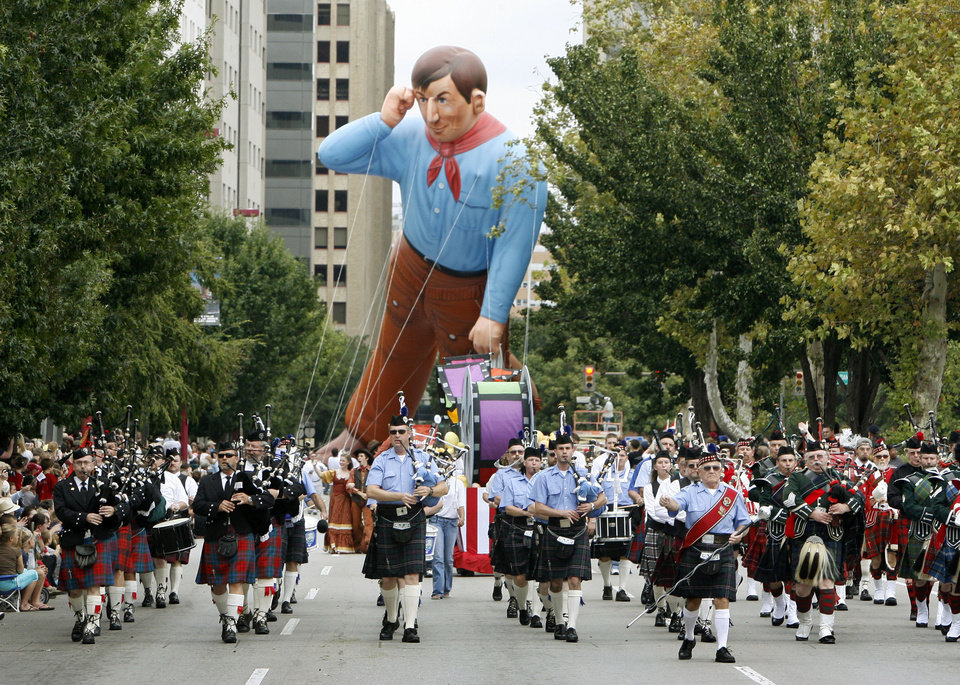 Photo - A giant helium filled Will Rogers looks over the Oklahoma Centennial Massed Pipes & Drums during the Oklahoma Centennial Parade in downtown Oklahoma City, Okla., Sunday, October 14, 2007. Photo by Paul Hellstern / The Oklahoman.