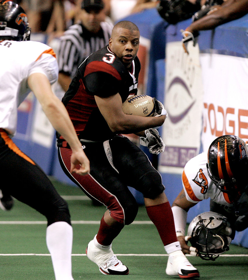 Photo - ARENA FOOTBALL LEAGUE 2, ARENAFOOTBALL2, PLAYOFFS: Jarrail Jackson of the Oklahoma City Yard Dawgz runs between Travis Snyder, left, and Tommy Balom of the Amarillo Dusters during their Arena 2 league playoff game at the Cox Convention Center in Oklahoma City, Saturday, August 6, 2005.  By Bryan Terry/The Oklahoman