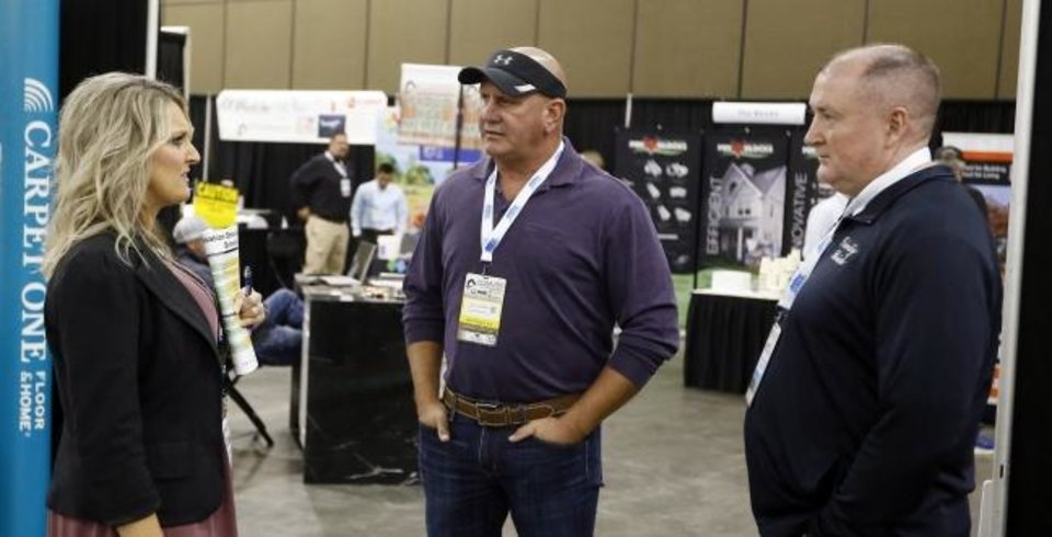 Photo -  From left, Robin Slater with CenterPoint Energy Inc., Jay London with Jay London Homes LLC, and James Ward with Trinity Brick Sales talk during the OK Building Summit & Expo at the Cox Convention Center. [NATE BILLINGS/THE OKLAHOMAN]
