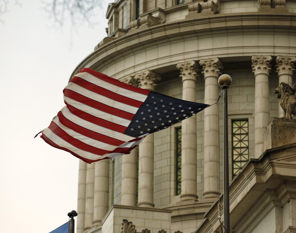 Photo - The American flag on the south plaza of the state Capitol flails in the wind after one corner was dislodged from flag pole when powerful winds passed through the Oklahoma City area Wednesday evening, March 24, 2015. Photo by Jim Beckel, The Oklahoman