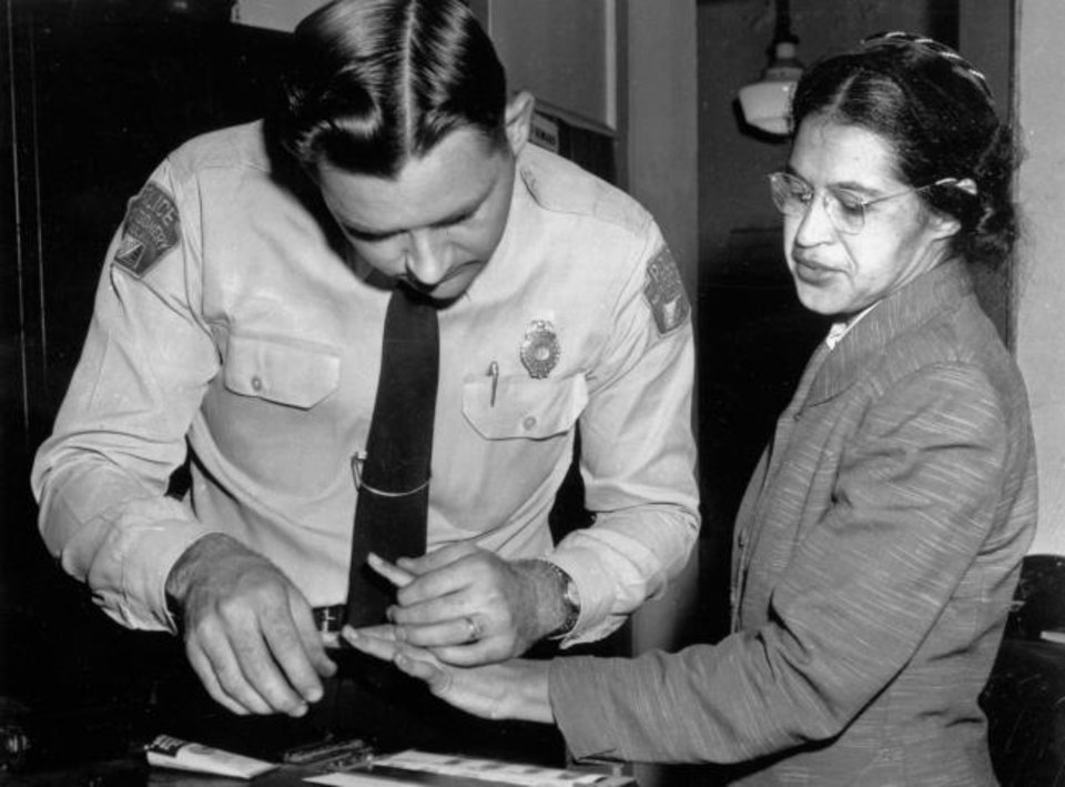 Photo -  In this Feb. 22, 1956, file photo, Rosa Parks is fingerprinted by police Lt. D.H. Lackey in Montgomery, Ala., two months after refusing to give up her seat on a bus for a white passenger on Dec. 1, 1955. She was arrested with several others who violated segregation laws. Parks' refusal to give up her seat led to a boycott of buses by blacks in December 1955. [AP FILE PHOTO]