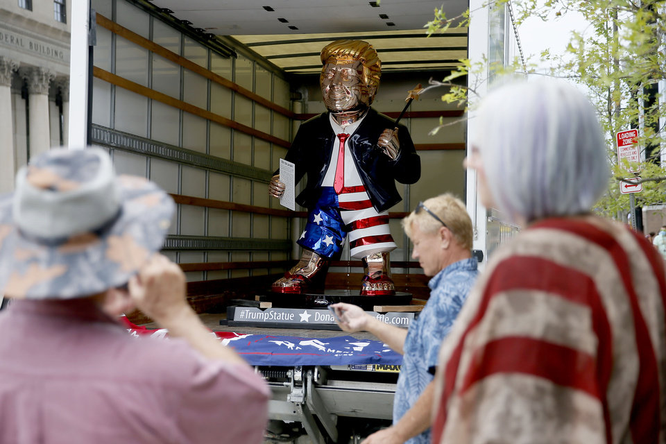 Photo - People take photos of a President Donald Trump statue before a rally at the BOK Center in Tulsa, Okla., Saturday, June 20, 2020. [Bryan Terry/The Oklahoman]