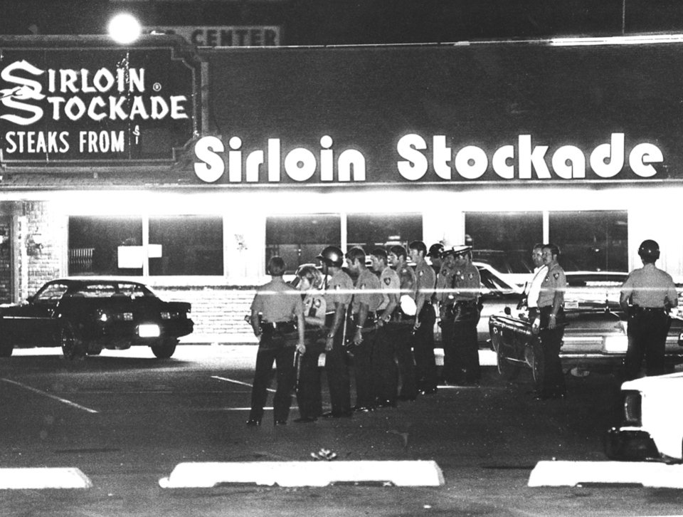 Photo -  Platoons of policemen descended on the Sirloin Stockade, 1620 SW 74, after the discovery of five slain employees and one fatally wounded worker on July 16, 1978. Officers combed every inch of the parking area in search for clues. Some dropped change was found, possibly robbery loot. [Oklahoman Archives photo]