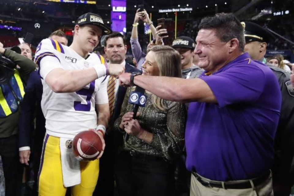 Photo -  LSU quarterback Joe Burrow and head coach Ed Orgeron celebrate after winning the SEC title on Dec. 7 in Atlanta. [AP Photo/John Bazemore]