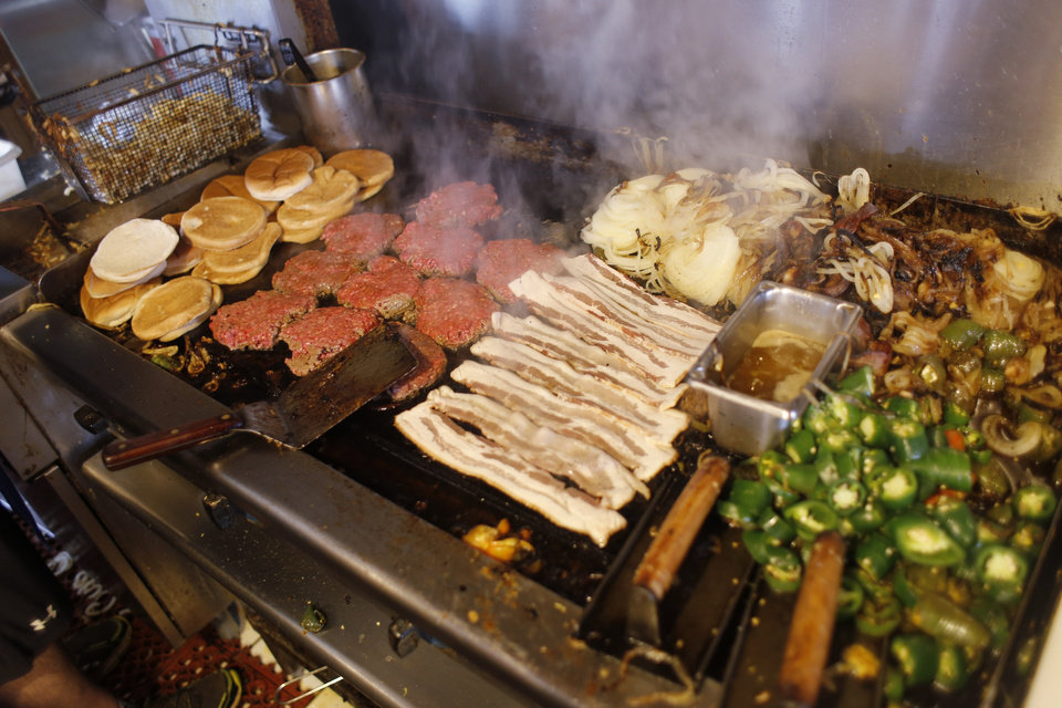 Photo -  The griddle at Nic's piles high with beef, bacon, jalapenos and onions as lunch progresses. Photo by Doug Hoke, The Oklahoman   DOUG HOKE - THE OKLAHOMAN