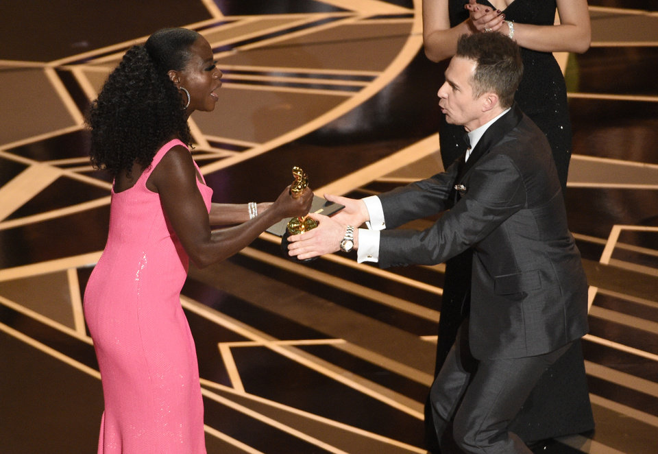 "Photo - Viola Davis, left, presents Sam Rockwell with the award for best performance by an actor in a supporting role for ""Three Billboards Outside Ebbing, Missouri"" at the Oscars on Sunday, March 4, 2018, at the Dolby Theatre in Los Angeles. (Photo by Chris Pizzello/Invision/AP)"