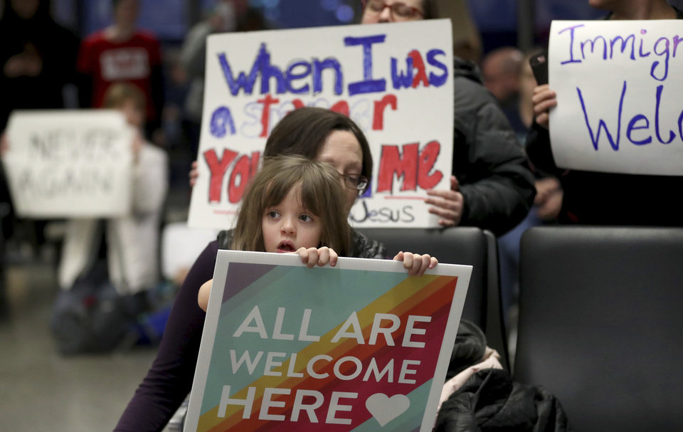 Photo - Rachel Walker, center, of St. Paul and her daughter Evelyn, 7, front, join others in protesting an executive order signed by President Donald Trump restricting immigration from several Muslim nations Saturday, Jan. 28, 2017, at the Minneapolis-St. Paul International Airport, in Minneapolis. (David Joles/Star Tribune via AP)