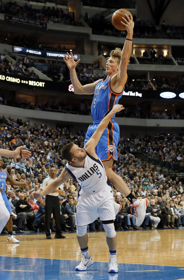 Photo - Oklahoma City Thunder forward Kyle Singler (5) goes up for an offensive rebound over Dallas Mavericks' J.J. Barea (5) of Puerto Rico in the first half of an NBA basketball game, Wednesday, Feb. 24, 2016, in Dallas. (AP Photo/Tony Gutierrez)