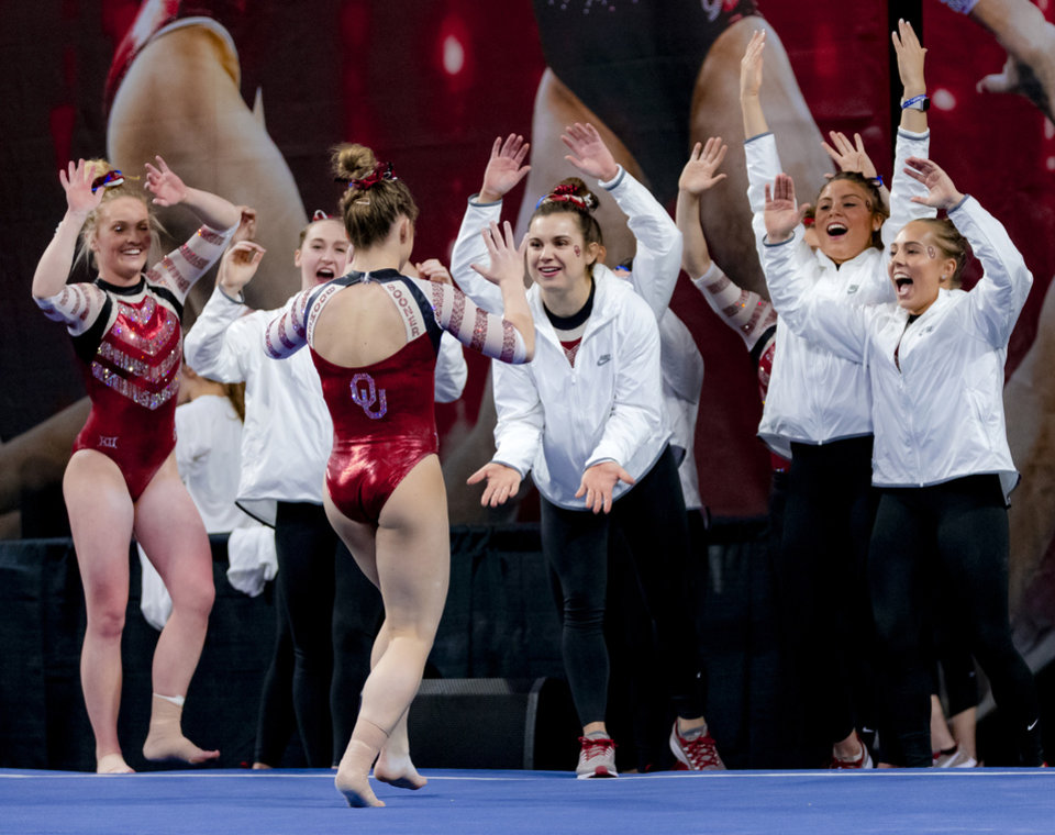 Photo - Teammates cheer after University of Oklahoma's Ragan Smith completes her floor routine during the women's gymnastics competition between the University of Oklahoma and Arkansas at the Lloyd Noble Center in Norman, Okla Monday, Jan. 20, 2020.   [Chris Landsberger/The Oklahoman]