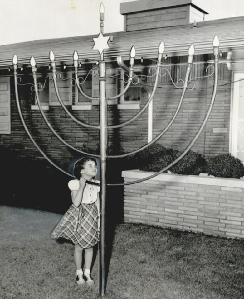 Photo -  In this 1953 photo, Joanna Benorf, 6, looks at the giant menorah on the lawn of Emanuel Synagogue in Oklahoma City.   [THE OKLAHOMAN ARCHIVES]