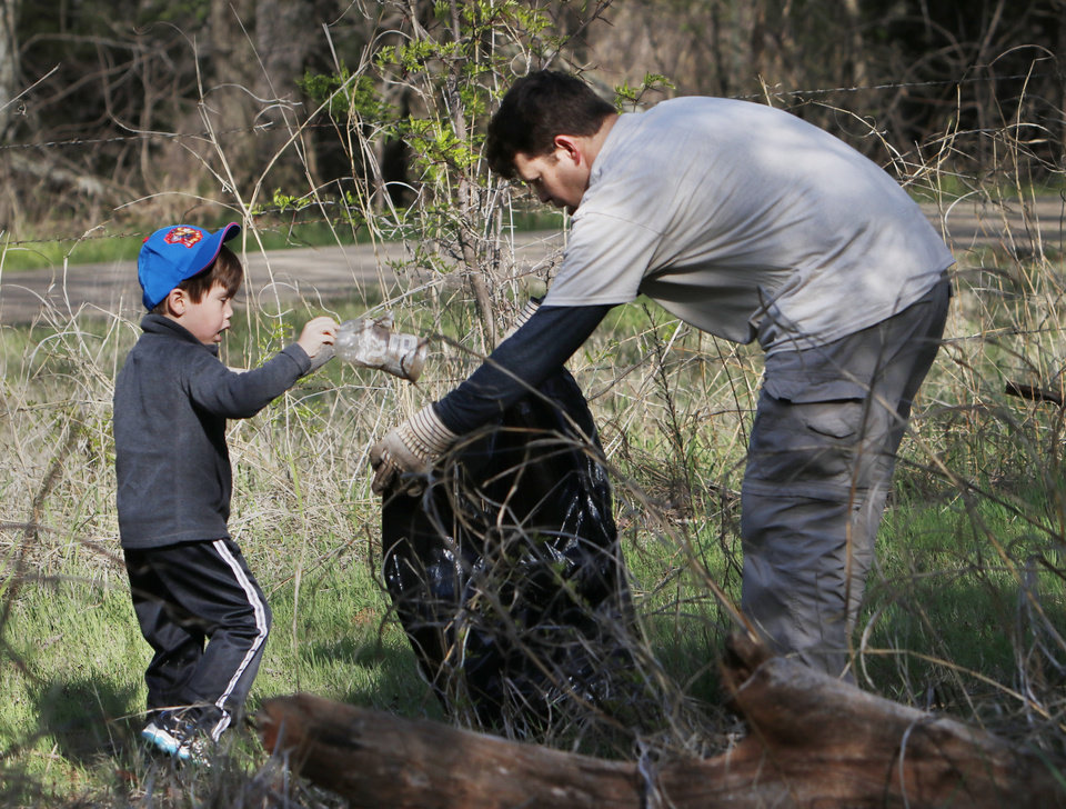 Photo -  Aaron Wendleboe and his son, Ian, 4, gather litter near a campground as volunteers participate in the annual Arcadia Lake Sweep. [PHOTO BY DOUG HOKE, THE OKLAHOMAN]