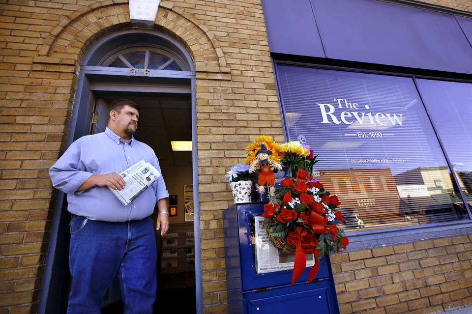 Photo - Todd Brooks stands in the doorway of the offices of  the Marlow Review newspaper on Main Street in downtown Marlow on Tuesday, Oct. 14, 2014. The newspaper was owned by Brooks' boss, John Hruby.   Brooks, a news and sports editor at the newspaper, discussed his reaction to the shocking  discovery of three members of a prominent Duncan family in their home, victims of a triple homicide in an upscale neighborhood on the north side of town Monday morning,  Oct. 13, 2014.  John and Tinker Hruby and their daughter, Katherine,  17, were found dead by the family's housekeeper. Townspeople and customers brought flowers to the paper's office Tuesday, leaving memorial wreaths and plants on a newspaper stand in front of the building.   Photo by Jim Beckel, The Oklahoman