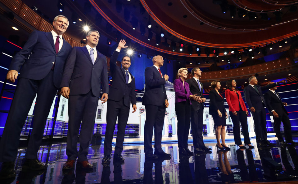 Photo - From left, New York City Mayor Bill de Blasio, Rep. Tim Ryan, D-Ohio, former Housing and Urban Development Secretary Julian Castro, Sen. Cory Booker, D-N.J., Sen. Elizabeth Warren, D-Mass., former Texas Rep. Beto O'Rourke, Sen. Amy Klobuchar, D-Minn., Rep. Tulsi Gabbard, D-Hawaii, Washington Gov. Jay Inslee, and former Maryland Rep. John Delaney pose for a photo on stage before the start of a Democratic primary debate hosted by NBC News at the Adrienne Arsht Center for the Performing Arts, Wednesday, June 26, 2019, in Miami. (AP Photo/Brynn Anderson)